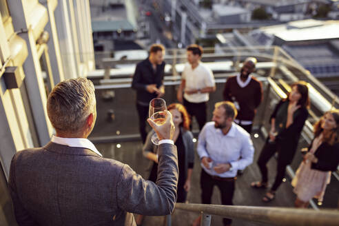 Mature businessman raising toast while giving speech to colleagues in terrace - MASF15903