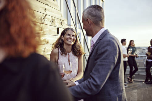 Smiling businesswoman talking with coworkers in party on terrace - MASF15915