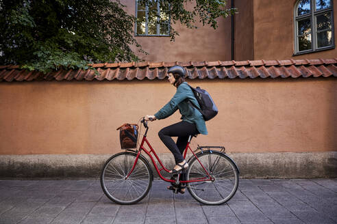 Side view of female engineer riding bicycle on street in city - MASF15936