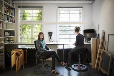 Portrait of female architect with coworker at table in office - MASF15969