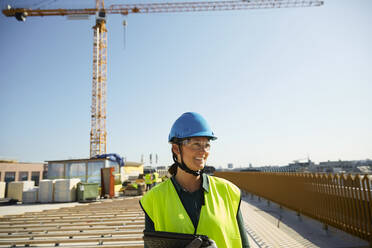 Smiling female engineer in reflective clothing with digital tablet at construction site against clear sky - MASF15981