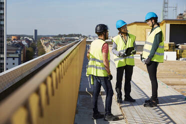 Male and female architects discussing at construction site - MASF15984