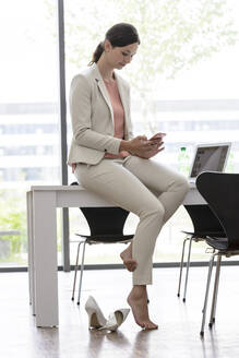 Young businesswoman using smartphone in office - BMOF00082