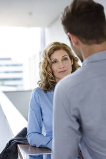 Businesswoman looking at businessman in office - BMOF00091
