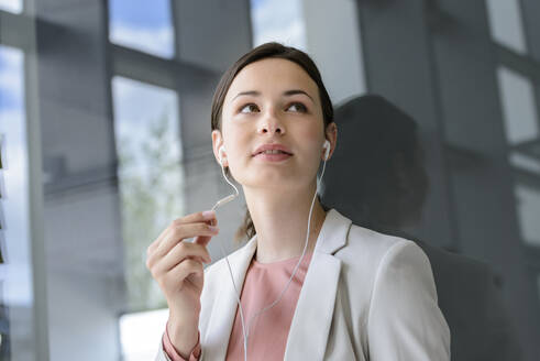 Young businesswoman with earphones in office - BMOF00100