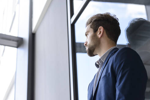 Young businessman leaning against the window - BMOF00103