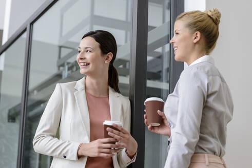 Two smiling businesswomen having coffee break outside office building - BMOF00106