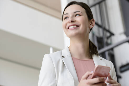 Happy young businesswoman with smartphone in office - BMOF00109