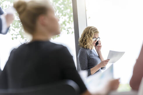 Businesswoman on the phone in office with colleagues in foreground - BMOF00121