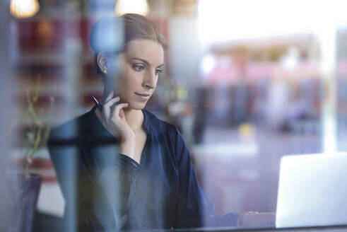 Businesswoman using laptop behind windowpane in a cafe - BMOF00124