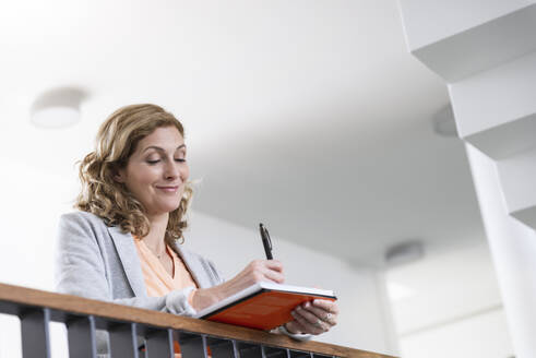 Smiling businesswoman taking notes in office - BMOF00139