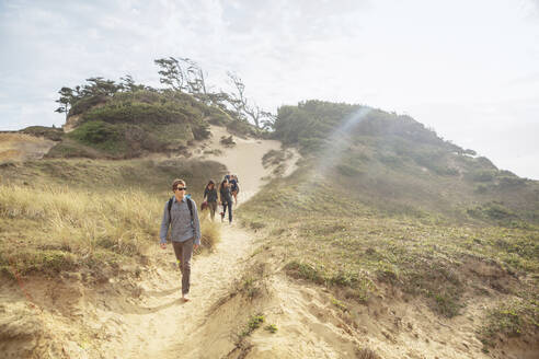 Friends walking on mountain against sky during summer - CAVF71067