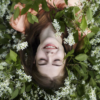 Overhead view of woman lying amidst plants - CAVF71251