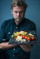Man holding platter with cheese and tomatoes - JOSF04112