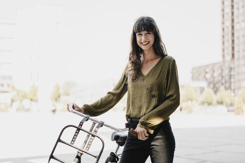 Smiling brunette woman with dutch roadster - KNSF06969