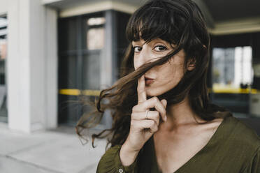 Portrait of smiling brunette woman, finger on mouth - KNSF06981