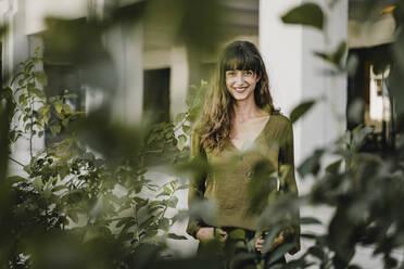 Portrait of smiling brunette woman behind plants - KNSF06984