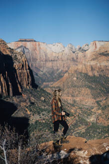Young girl posing with a camera with Zion National park as background - CAVF71356