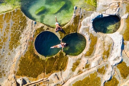 Aerial view of couple floating at figure eight pools at Sydney's Royal National Park, Australia. - AAEF06103