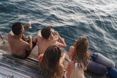 Friends enjoying champagne on sailboat, Italy - CUF54189