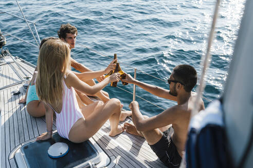 Friends toasting with beer on sailboat, Italy - CUF54216