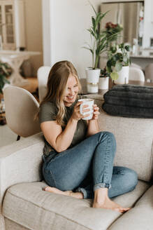 Woman relaxing on sofa with warm beverage - ISF23466