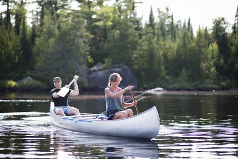 Friends canoeing on lake against trees - CAVF72459