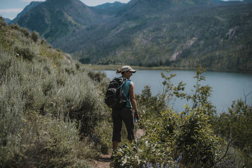 Rear view of female hiker with backpack standing on field amidst plants at lakeshore against mountains - CAVF72468