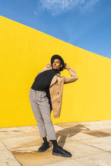 Young man dancing in front of yellow wall - AFVF04535