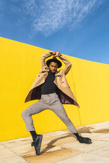 Young man dancing in front of yellow wall - AFVF04538