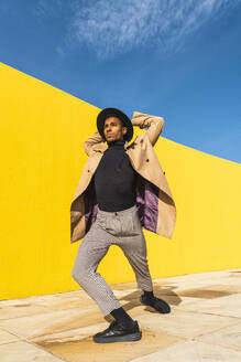 Young man dancing in front of yellow wall - AFVF04541