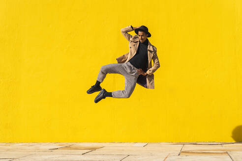 Young man dancing in front of yellow wall, jumping mid air - AFVF04544