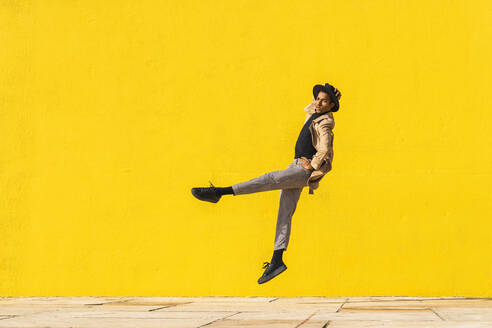 Young man dancing in front of yellow wall, jumping mid air - AFVF04547