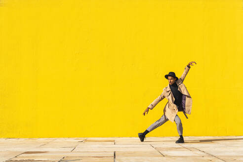 Young man dancing in front of yellow wall - AFVF04553