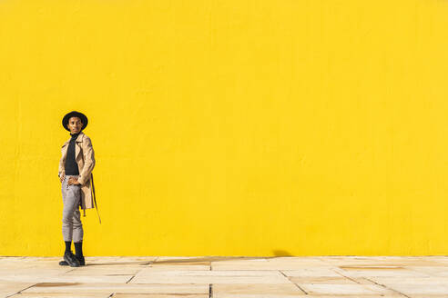Young man dancing in front of yellow wall - AFVF04556