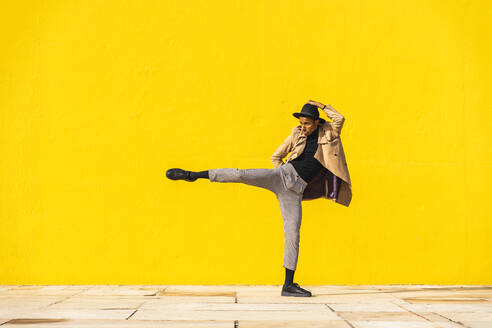 Young man dancing in front of yellow wall - AFVF04559