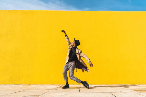 Young man dancing in front of yellow wall, taking selfies - AFVF04574