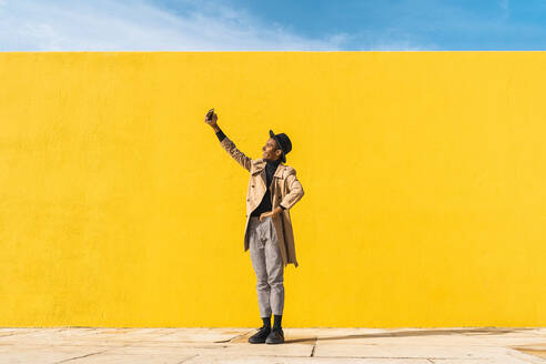 Young man dancing in front of yellow wall, taking selfies - AFVF04577