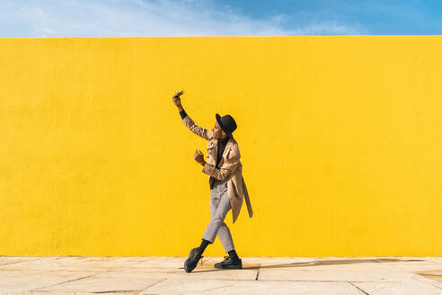 Young man dancing in front of yellow wall, taking selfies - AFVF04580