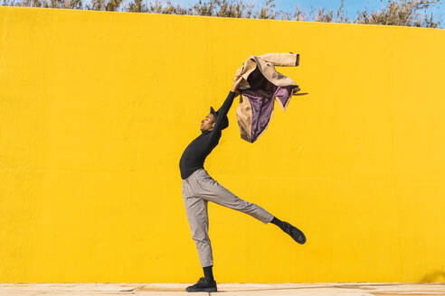 Young man dancing in front of yellow wall - AFVF04583