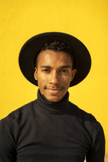 Portrait of young man, wearing black in front of yellow wall - AFVF04586