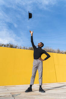 Young man with black hat, dancing in front of yellow wall - AFVF04595