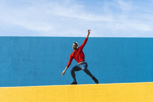 Young man with headphones, listening music, dancing on yellow wall - AFVF04604