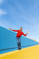 Young man with headphones, listening music, dancing on yellow wall - AFVF04607