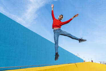 Young man with headphones, listening music, dancing on yellow wall - AFVF04613