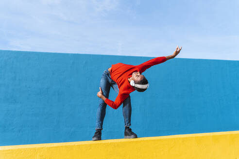 Young man with headphones, listening music, dancing on yellow wall - AFVF04616