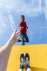 Young man with headphones, dancing for person, leaning on yellow wall - AFVF04619