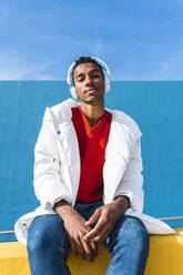 Young trendy man sitting on yellow wall, listening music - AFVF04625