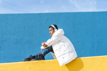 Young trendy man sitting on yellow wall, listening music - AFVF04631