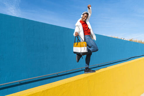 Young man with bag, dancing carefree on a yellow wall - AFVF04634